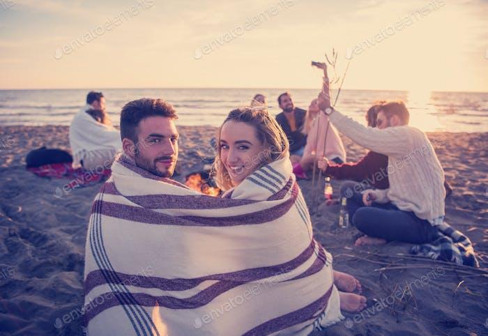 Pareja disfrutando con Amigos al atardecer en la Playa