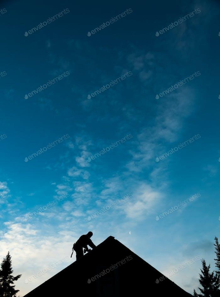 Bauunternehmer in Silhouette arbeiten auf einem Dach Top