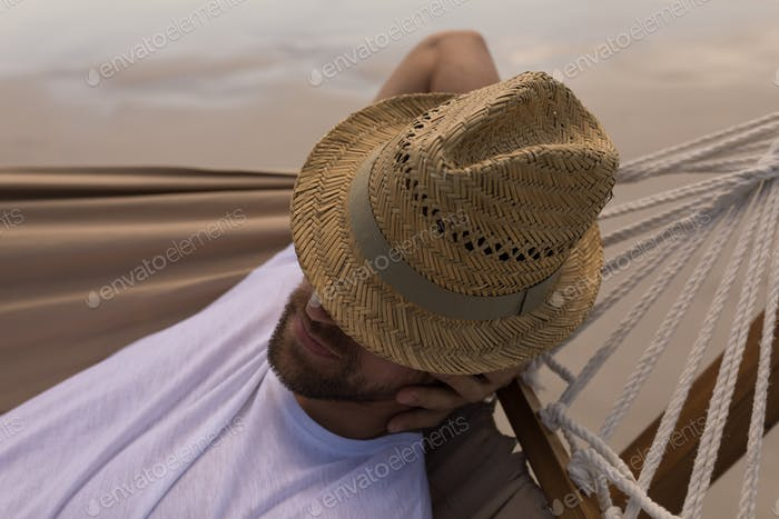 Young man with hat and hand behind hand relaxing on hammock at beach