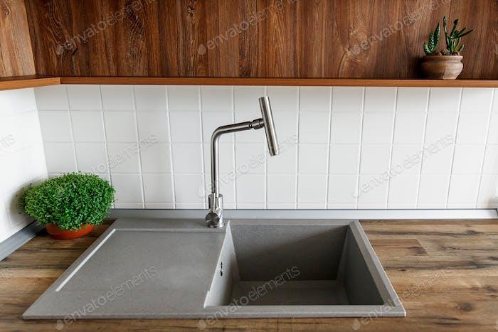Stilvolle Granitspüle mit moderner Wasserhahn in Holzarbeitsplatte