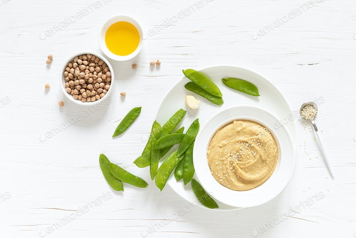 Homemade chickpea hummus served with green peas, healthy vegetarian food concept, top view
