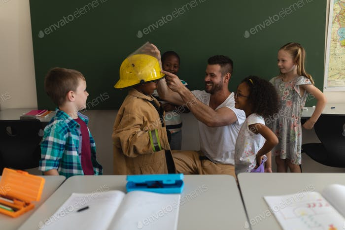 Male firefighter helping a schoolkid to wear fire uniform in classroom