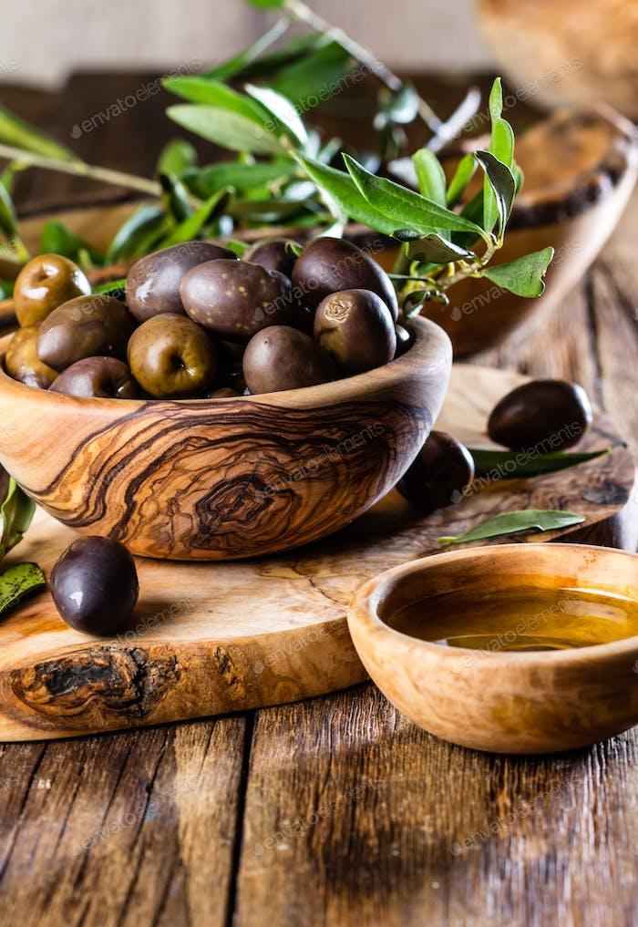 Olives and olive oil in olive wooden bowls, olive tree branch