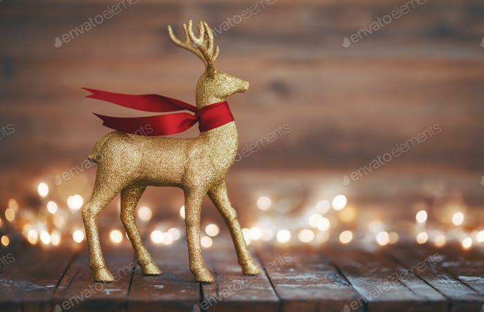 Golden reindeer on wooden background
