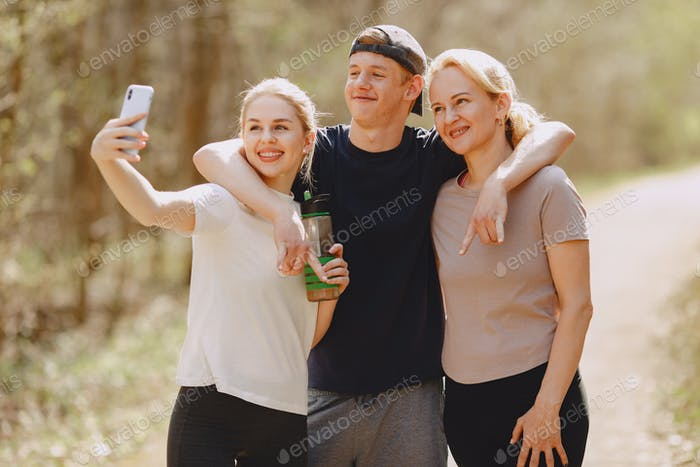 Sports family standing in a summer forest