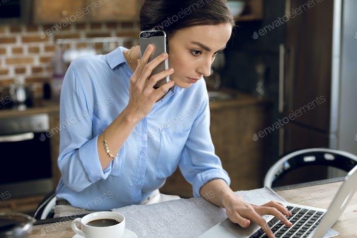 Концентрированная молодая женщина разговаривает на смартфоне во время использования ноутбука