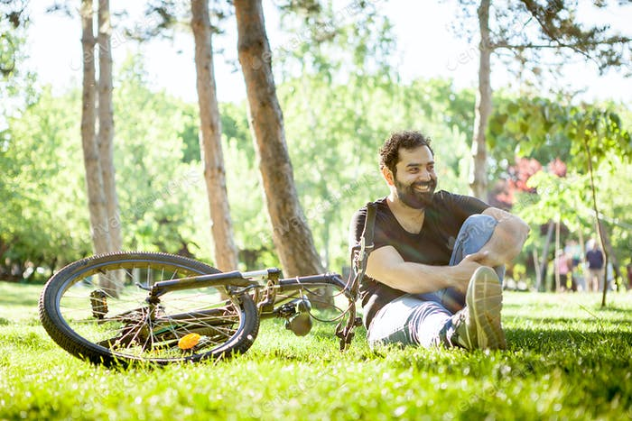 Young bearded man smiles to the camera sitting on the ground in the grass
