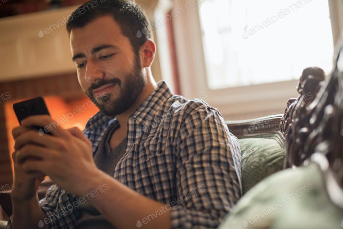 A man checking his cell phone and smiling.