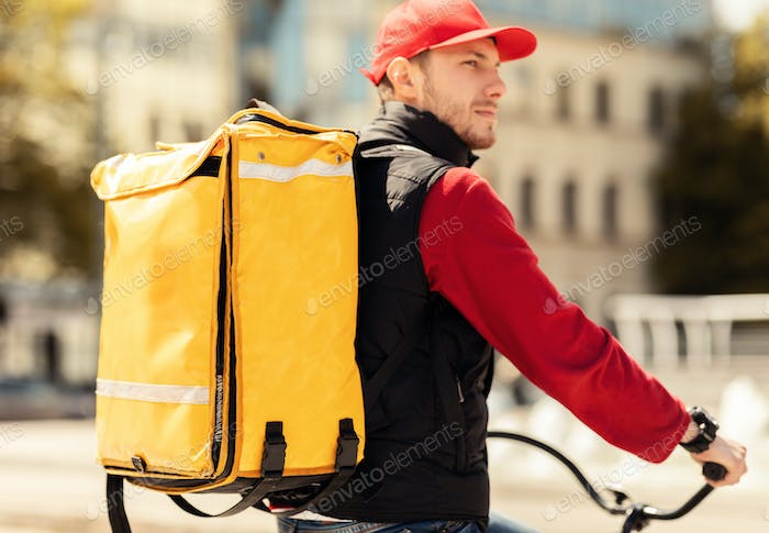 Delivery Guy Riding Bike Outdoors In Urban Area Delivering Food