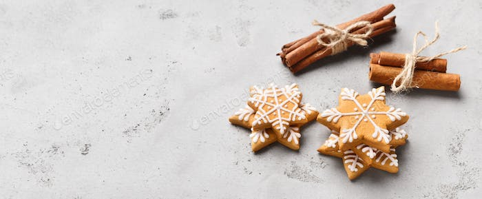 Christmas gingerbread cookies and cinnamon sticks on grey background