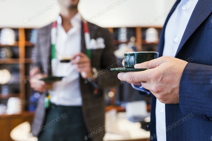 Tailor and customer drinking coffee in clothing store