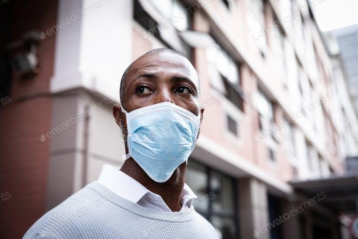 Afroamerikaner tragen covid19 coronavirus Maske auf der Straße