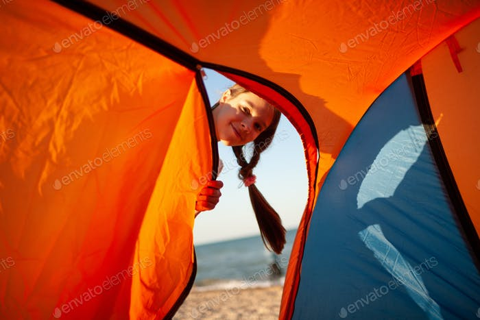 Beautiful cheerful girl stands near a bright tent and smiles looking at the camera