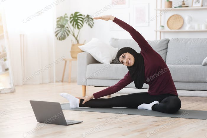 Arabic Woman Doing Fitness Exercises At Home, Watching Online Tutorials On Laptop