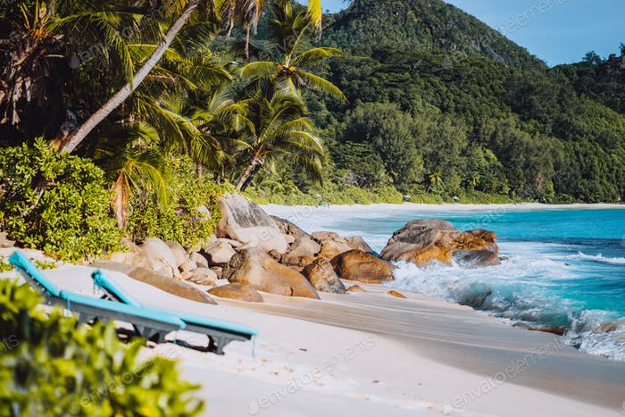 Mahe, Seychelles. Two sun lounger at secluded Anse intendance beach. Ocean waves rolling to shore