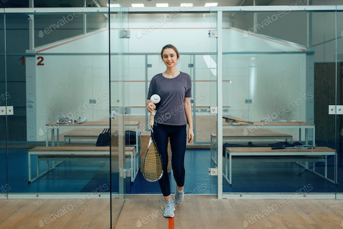 Female player with squash racket in locker room