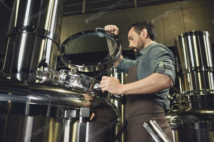 Male brewer in apron inspecting tank at the brewery