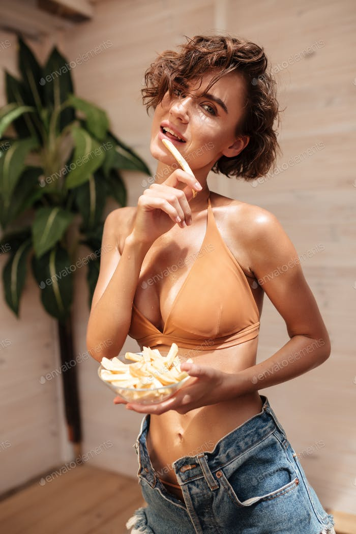 Pretty girl in beige bikini and denim shorts standing with bowl of fried potatoes in hands