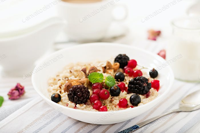 Tasty and healthy oatmeal porridge with berry, flax seeds and nuts.