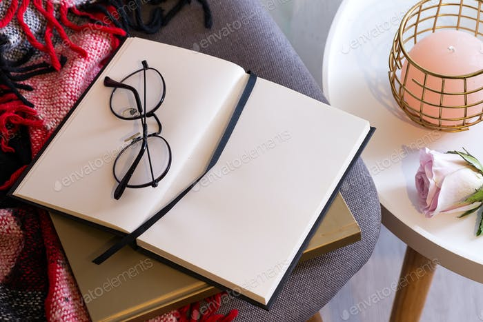 Notebook with glasses on a red plaid . Concept comfort