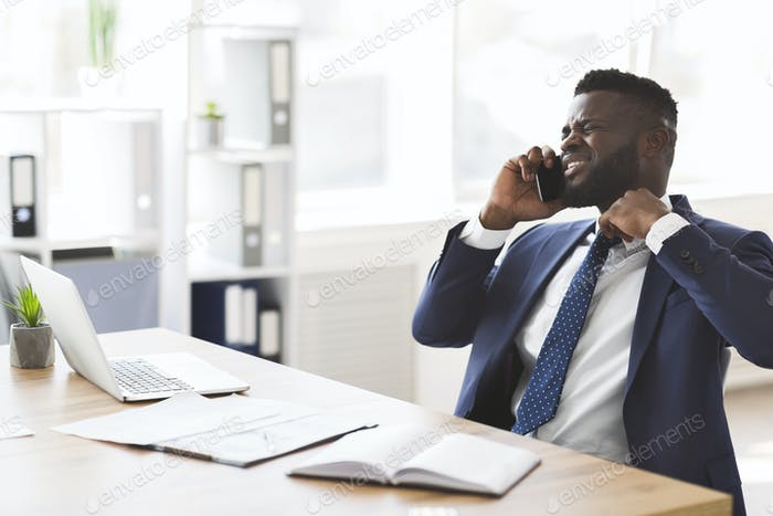 Stressed young manager talking by phone with colleagues