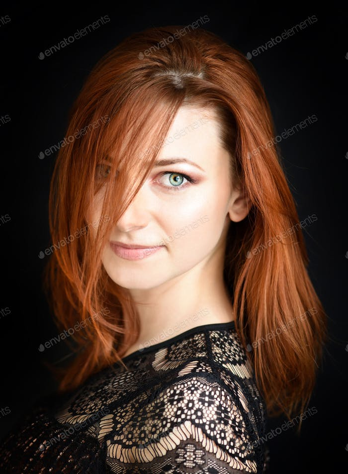 Portrait of a beautiful young woman with long red hair on a dark