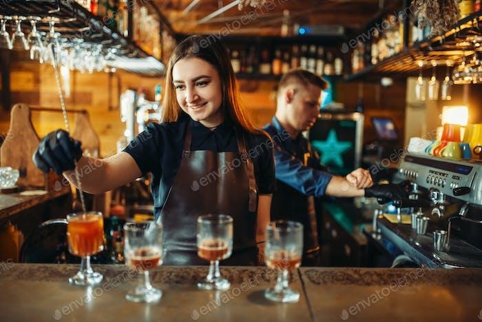 Männliche und weibliche Barkeeper an der Theke