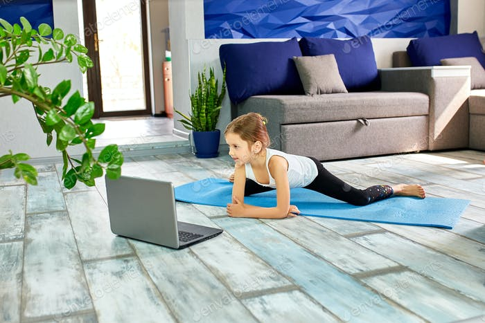 Little cute girl in sportswear on blue mat practicing gymnastics at home