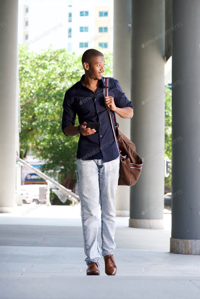 cool black guy walking in the city with mobile phone and bag