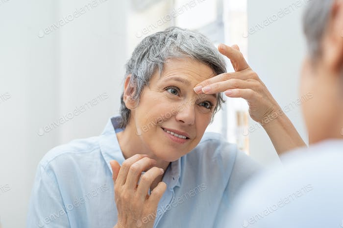 Mature woman looking her wrinkles face