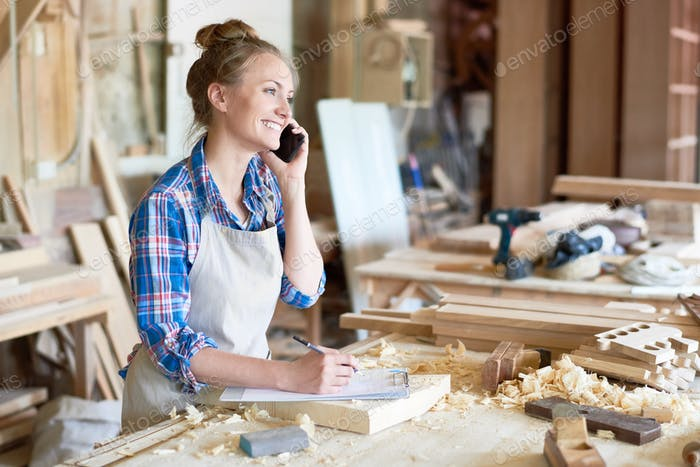 Young Woman Speaking By Smartphone in Modern Joinery