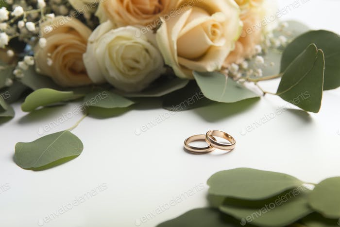 Wedding rings with roses on white background