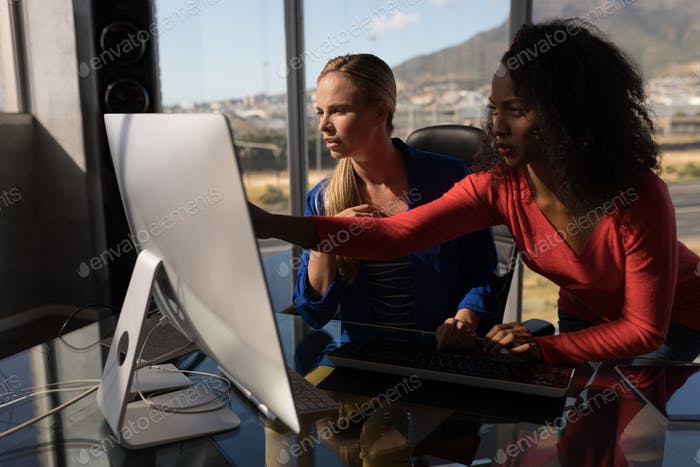 Female executives working together on desktop pc in office