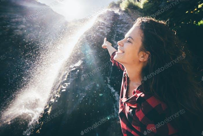 Joven chica feliz disfrutando de la cascada.