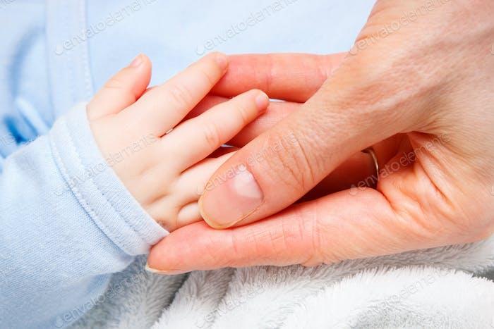 Hand of newborn baby in hand of mother