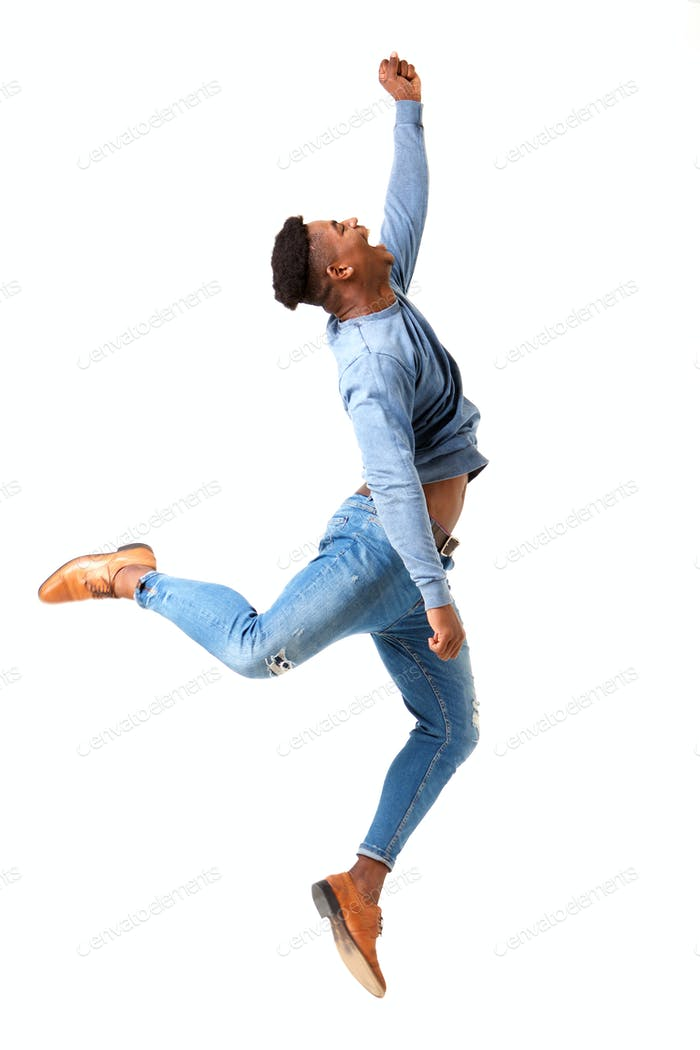 Full body profile of happy young black man jumping for joy against isolated white background