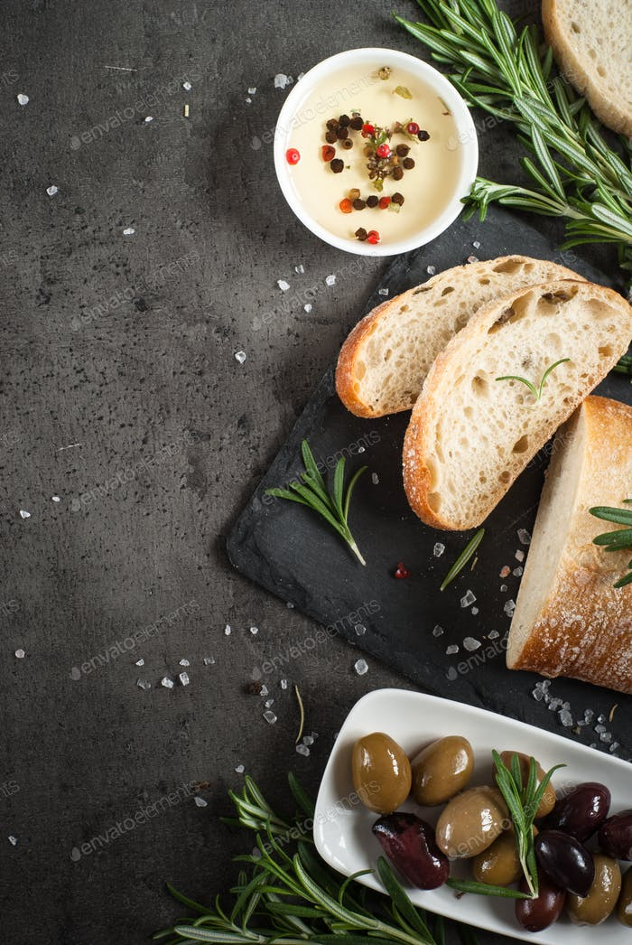 Italian ciabatta bread  on black slate with herbs and olives.