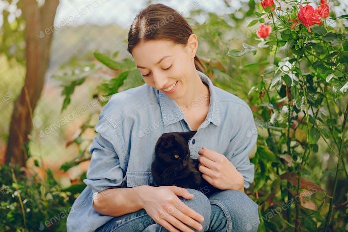 Mädchen in einem blauen Hemd spielen mit niedlichen Kätzchen