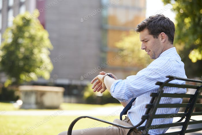 Businessman Sitting In City Park Looking At Smart Watch