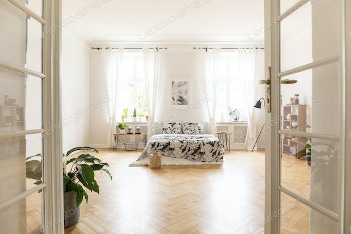 Sun shinning through windows into a spacious stylish bedroom int