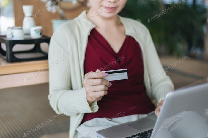 Cropped view of woman pays by credit card for an e-commerce