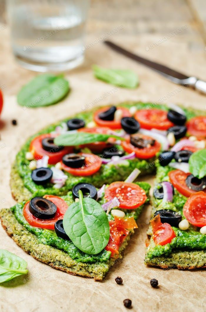 vegan broccoli zucchini pizza crust with spinach pesto, tomatoes
