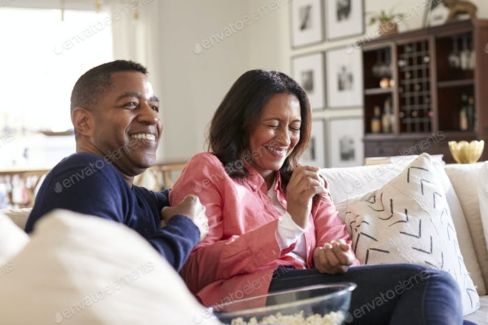 Close up of middle aged couple sitting on the sofa in their living room watching TV,