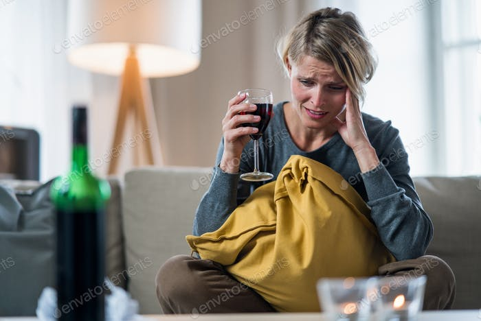 Depressed woman indoors at home, mental health and alcohol addiction concept