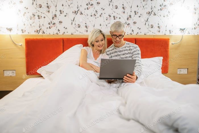 Mature couple looking on laptop in bedroom