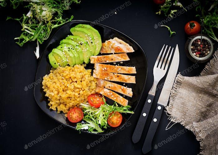 Gesundes Gericht mit Huhn, Tomaten, Avocado, Salat und Linsen