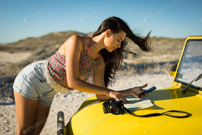 Happy caucasian woman reading roadmap on beach buggy by the sea
