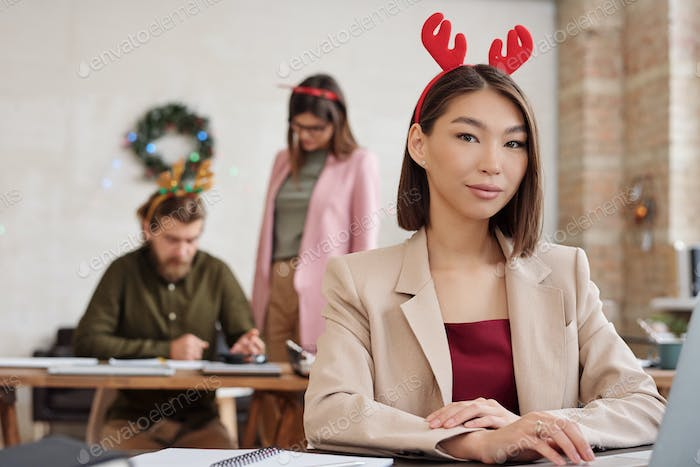 Young brunette manager in smart casualwear and xmas headwear networking
