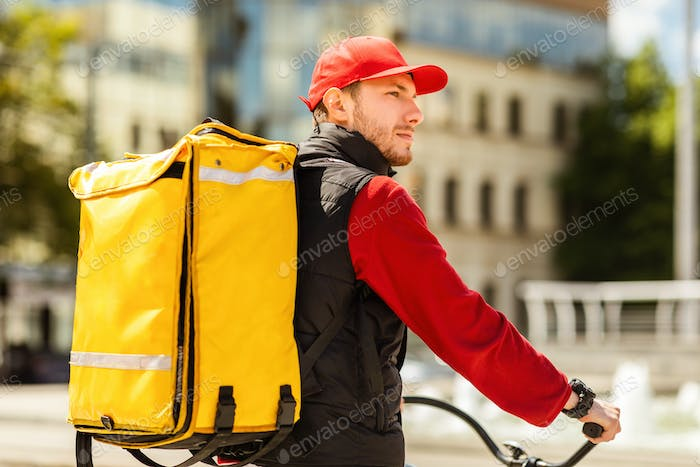 Courier With Yellow Backpack Delivering Food On Bicycle Riding Outside