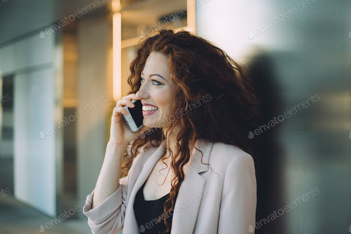 Happy beautiful young redhead woman doing shopping and speaking